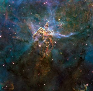 This turbulent cosmic pinnacle lies within a tempestuous stellar nursery called the Carina Nebula, located 7500 light-years away in the southern constellation of Carina. The image marks the 20th anniversary of Hubble's launch and deployment into Earth orbit. Scorching radiation and fast winds (streams of charged particles) from hot newborn stars in the nebula are shaping and compressing the pillar, causing new stars to form within it.