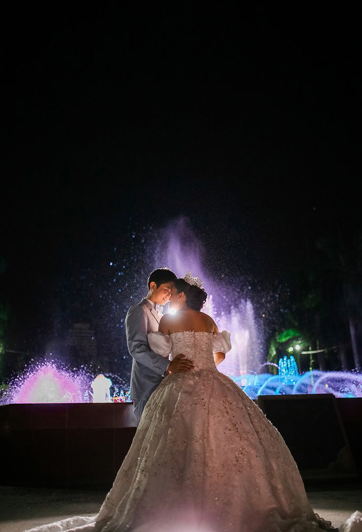 Cinderella bride and her Prince Charming groom slow dance to lighted water fountain displays under the starry night // Cinderella married her Prince Charming in Manila, Philippines! Nikko and Janna's wedding saw the bride wearing a puffy-sleeved wedding gown of her own design, with her bridesmaids dressed as Disney princesses.