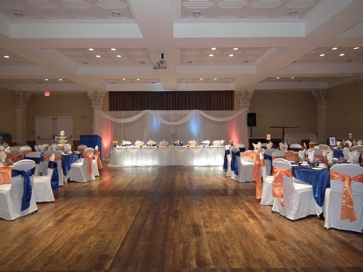 London, Ontario - Wedding Reception hall - Mocha Shriners' Hall on Colborne Street - Wedding Decor by High Gloss Weddings -www.highglossweddings.com - Orange & Royal blue - satin linens - uplighting - overlays & sashes - Head table - back drop