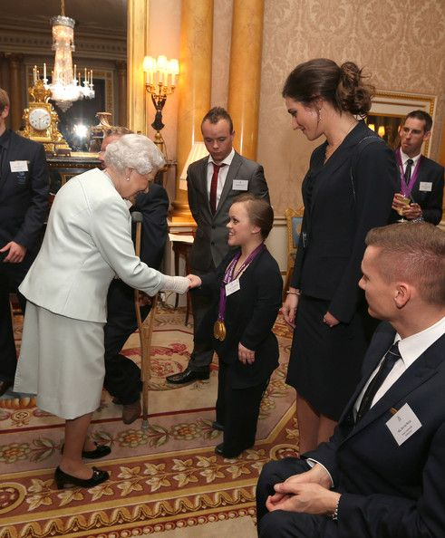 Queen Elizabeth II meets swimmer Eleanor Simmonds during a reception for the Team GB Olympic and Paralympic medalists at Buckingham Palace on October 23, 2012 in London, England.