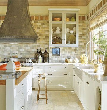 Kitchen Details  Large-scale decorative nailheads, one of the interior designer's favorite decorative touches, dot the custom range hood in the kitchen and the counter-height bar.  Subway wall tiles in a mix of neutral tones provide visual interest.  Extra details on the cabinetry, such as paneled drawers and carved posts, set this kitchen apart.