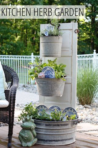 Vertical herb garden made from an old door, galvanized bins and serving ware.