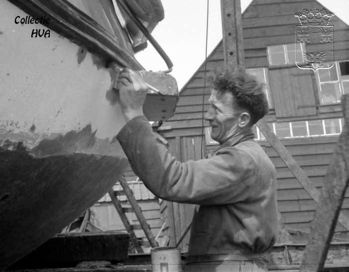 Kees Meerman, de werfbaas werkt de huid van een schip bij.   In 1964 was er een wedstrijd voor de beste foto van 'de Werkende Mens'. In dat kader werd deze foto gemaakt