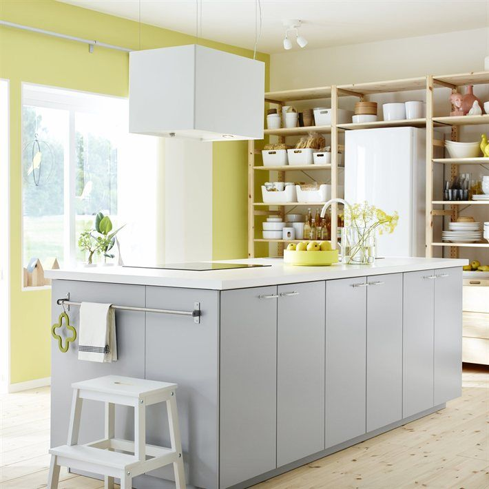 Kitchen with open wooden shelves, a freestanding kitchen block in grey and white and a wall in pastel green by IKEA