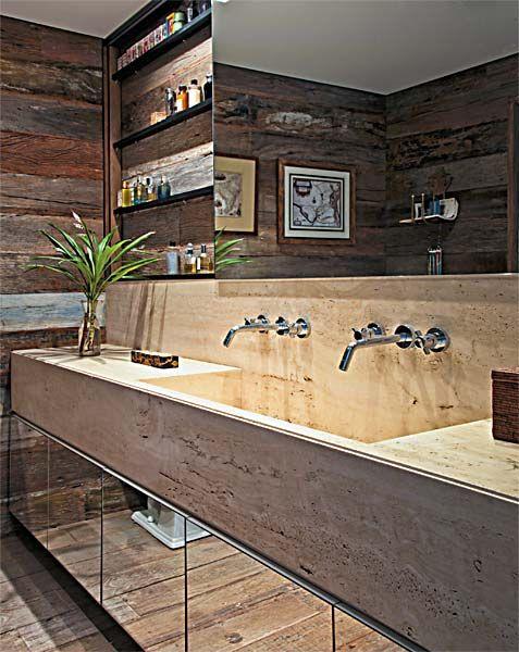 Bancada de travertino romano – leva apenas proteção de resina incolor. Em paredes e pisos, assoalho de peroba-rosa de demolição bruta e escovada.