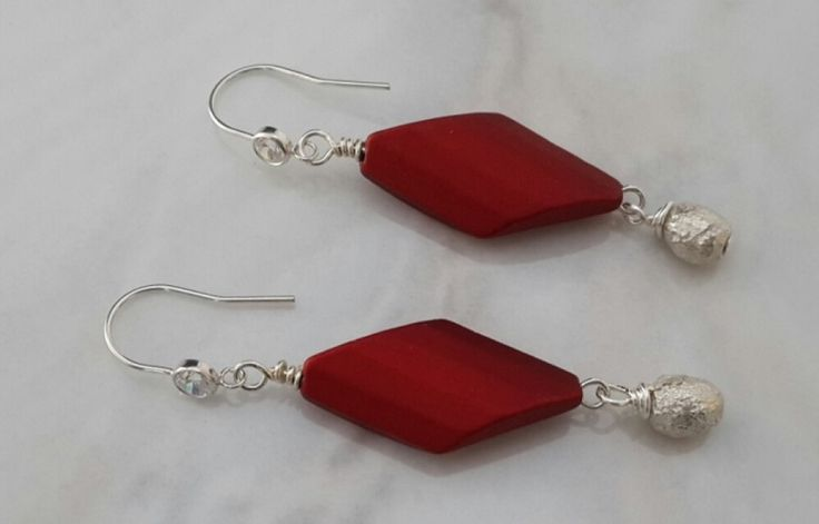Elegant satiny red resin bead hanging from cubic zirconia earwires with a crumpled silver bead beneath. Hand made - One pair only