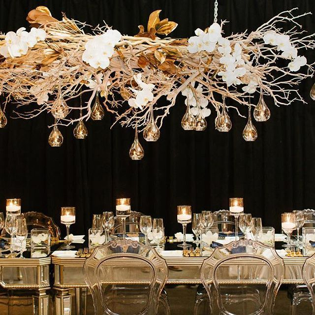 Talk about a jaw-dropping design! Manzanita branches woven with cascading #orchids and antique gold magnolia leaves were suspended from chain link hanging from the ceiling over tables at this #FermentingCellar #wedding. | WedLuxe Magazine | #luxury #weddinginspiration #centerpiece #tabledecor #weddingdecor