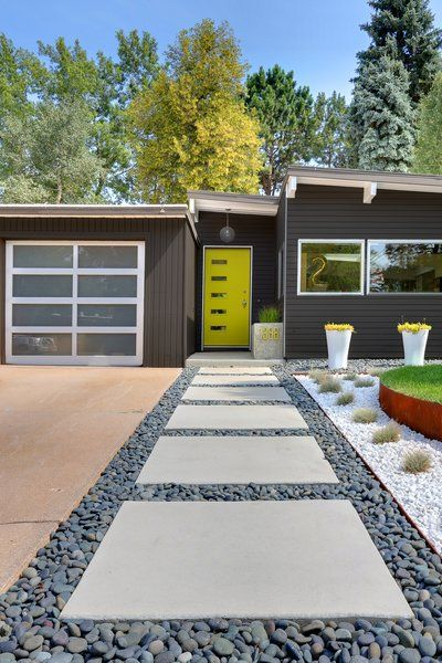 Generous concrete pavers lead to the entrance. The home's angles are typical of the midcentury homes in the neighborhood. Tagged: Outdoor, Front Yard, Walkways, and Hardscapes. Photo 2 of 6 in A Low-Maintenance Landscape for a Midcentury Denver Home by Erika Heet