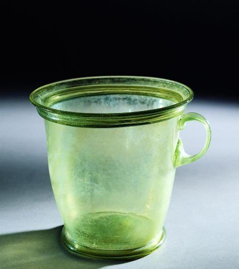 """VETRI POMPEIANI.  Modiolus  Questo bicchiere, di altezza pari a circa 11 cm (Sanp n. inv. 4960), di forma troncoconica ed ansa a """"nastro"""" posta appena sotto il labbro, venne rinvenuto nel 1932 nella Casa del Menandro (I.10.4). Ottenuto con la tecnica della soffiatura, presenta riflessi verdolini. Fu probabilmente prodotto da delle officine di area vesuviana che durante il I sec. d.C. erano da annoverare tra i principali centri di lavorazione di questo tipo di contenitori. #pompeii…"""