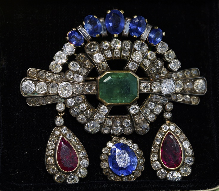 This antique brooch from the 1850's boasts all the hallmarks of the Early Victorian Era, including a romantic feel, colored gemstones and of course diamonds. With tear-drop shaped Burmese rubies, striking Ceylon sapphires with a lustrous light blue color, and a show-stopping emerald in central position, this substantial brooch is bright yet elegant. With a commanding feel of authority, its shape is even reminiscent of a British medal of honor.