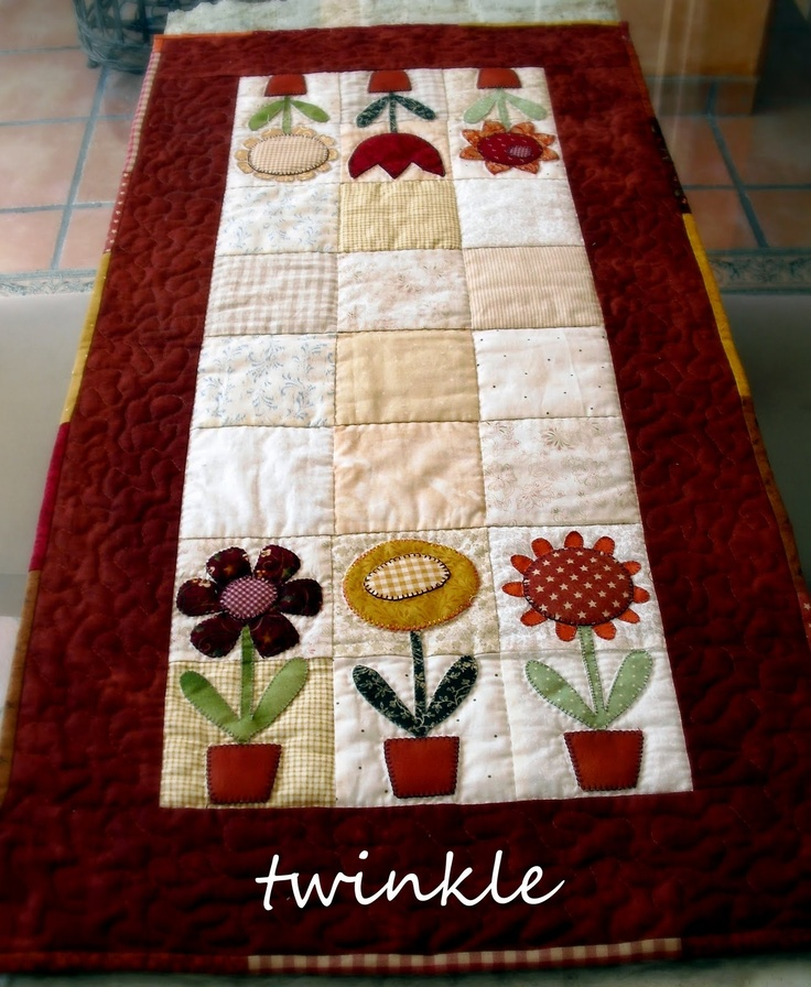 This looks like a Kim Schaefer quilt. Love the simple flowers as a table runner!