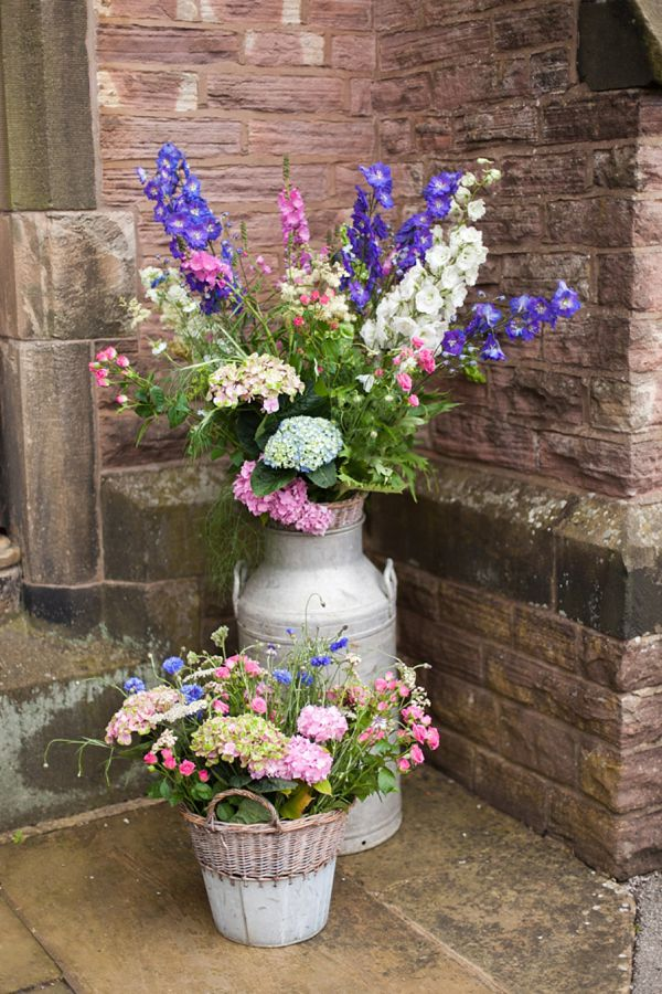 Country garden flowers in a milk churn for a eco friendly wedding. Photography by www.victoriaphippsphotography.co.uk