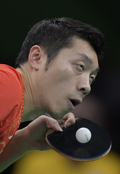 China's Xu Xin eyes the ball as he serves against Britain's Paul Drinkhall in…