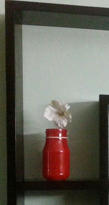 An empty mason jar is all you need to create magic! Paint it red and decorate it with a lovely white flower.