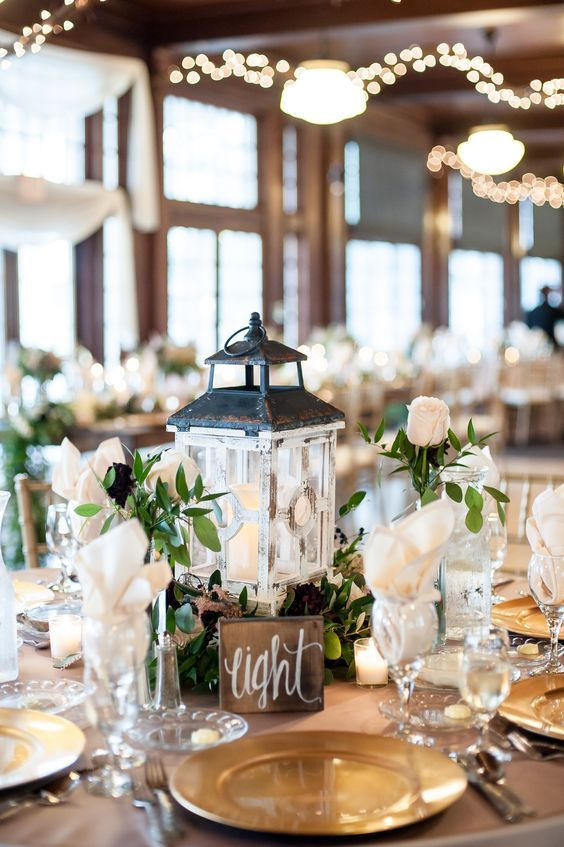 Rustic lanterns resting in lush floral wreaths make for lovely centerpieces / http://www.himisspuff.com/100-unique-and-romantic-lantern-wedding-ideas/8/