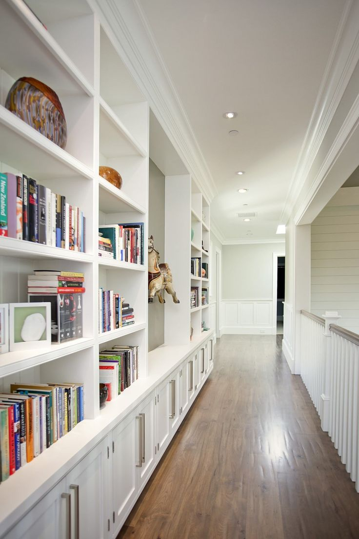 Smart Ways to Add Hallway Storage in Your Home : Beige Wall For Modern Hall Design With Hallway Storage And Built In Bookcase Also White Wainscoting Plus Wood Flooring And White Railing Also Hallway Lighting
