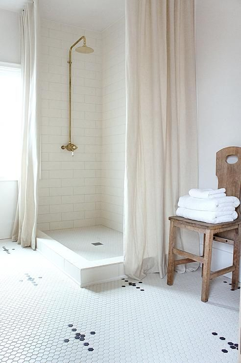 exquisite white bathroom features a corner white subway tiled walk in shower boasting a vintage brass