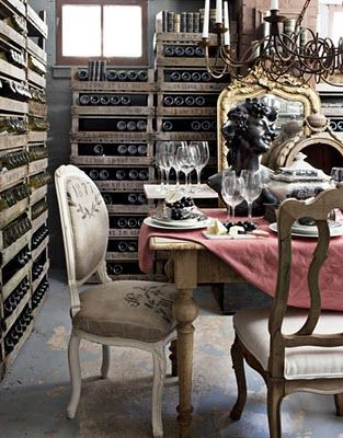 The guilded mirror offers a bit of opulence among the rustic wine racks and burlap chairs. Oh, and notice the bust on the table-very Paris Apartment.