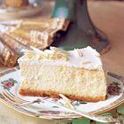Mascarpone-citroentaart : - 150 g gemberkoekjes - 70 g boter, gesmolten - 400 g roomkaas - 250 g mascarpone - 150 g fijne tafelsuiker - sap en geraspte schil van 1 citroen - 4 grote eieren,  Voor het glazuur en de versiering - 200 ml crème fraîche of zure room - 1 eetlepel fijne tafelsuiker - ¼ theelepel vanille-essence - wittechocoladekrullen of rozenblaadjes