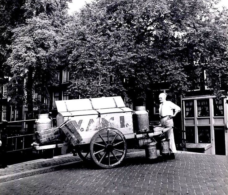 1950. A milkman of VAMI with push cart on the Welfbrug at the Reguliersgracht in Amsterdam. The Reguliersgracht and canal houses were constructed as part of the 4th expansion of the city in 1658. The canal connect the Herengracht with the Lijnbaansgracht and crosses the Prinsengracht and Keizersgracht. The VAMI (Verenigde Amsterdamse Melkinrichtingen) was a dairy products brand with milk factory at the Overtoom in Amsterdam. Photo Cas Oorthuys. #amsterdam #1950 #Reguliersgracht #VAMI