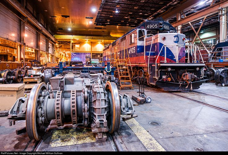 """Shop Floor""  Its a quiet night Saturday night in the MMC shops. One of Metro-North's six GP40FH-2s sits in the MMC Loco Shop undergoing maintenance. The West-of-Hudson EMD sits next to a series of ALP46 power combos awaiting installation."