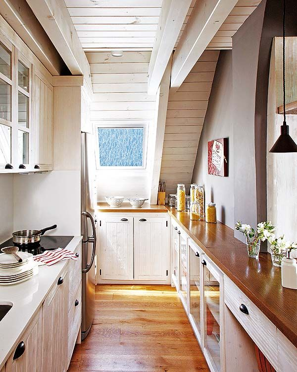 Narrow galley kitchen white glass-front cabinets, wood floors, door on end, wooden countertops, exposed beams
