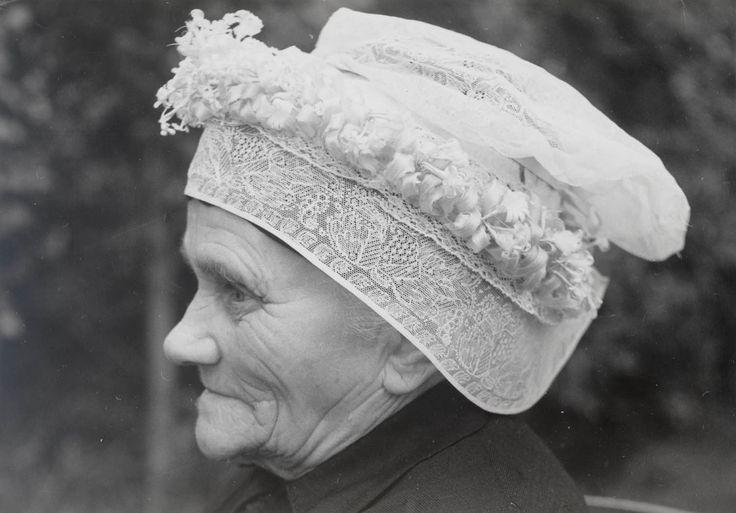 Mevrouw Kee van Eekelen-De Kok uit De Kladde (N-B) demonstreert opzetten van strakke muts. Haar in knot op achterhoofd vastgestoken. Vervolgens wordt zwart band met 2 strengetjes vals haar om voorhoofd vastgebonden. Vervolgens zwarte ondermuts met bandjes om hoofd vastgezet. Over de ondermuts komt vervolgens de 'strakke muts', met een bol en voorstrook van kant. Tot slot komt over de 'strakke muts' een bandje, versierd met lussen van lichtblauw lint en kunstbloemetjes. 1956 #NoordBrabant
