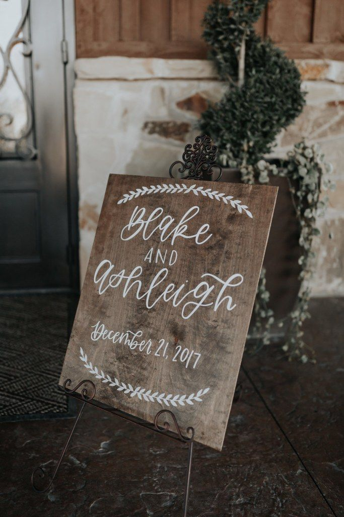 Gorgeous, natural wedding sign to welcome your guests into your wedding venue. Love the simplicity of this sign!  A stained wooden board with the couple's names and the wedding date.  Such a cute piece of home decor after the wedding day as well! Photo taken at THE SPRINGS Event Venue.  Follow this pin to our website for more information, or to book your free tour! SPRINGS location:  Edmond, OK Photographer:  Shelby Seaber Photography #weddingsign #naturalwedding #weddingdecor