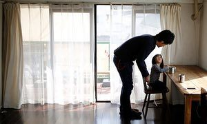 Three shirts, four pairs of trousers: meet Japan's 'hardcore' minimalists: Minimalist Naoki Numahata talks to his two-and-a-half year old daughter Ei in their living-room in Tokyo.