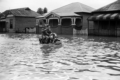 Two men riding a motorbike during the Maitland Flood, 1955: Lucey Collection