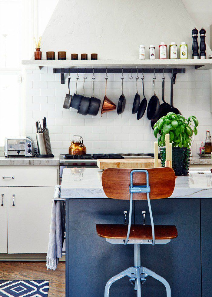 Marble kitchen island and hanging pots rack above stove subway tiles