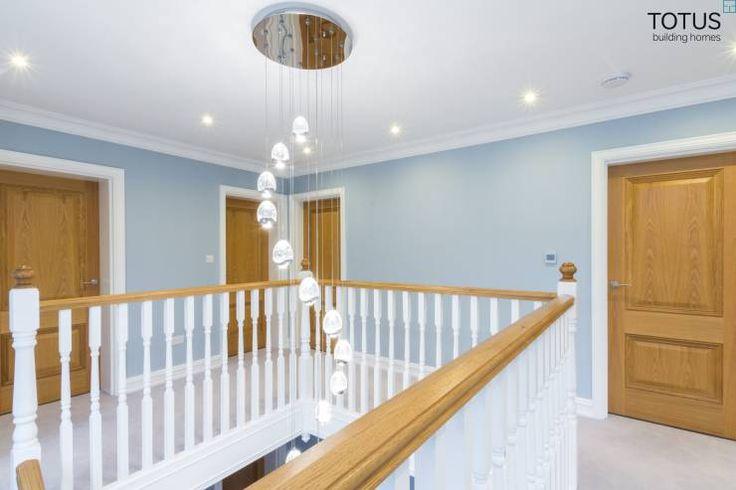 Delicado e moderno, o conjunto de luzes pendentes se desenrola sobre o fosso da escada, iluminando os degraus indiretamente. O corredor no alto da escada recebe luzes embutidas em toda a extensão do teto, o que intensifica a quantidade de luz disponível no ambiente. A cor clara da escada, que combina guarda-corpo branco e corrimões em madeira acentua a luminosidade da luminária de teto. Para outras dicas sobre iluminação