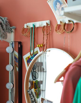 KOLJA mirror with MUSIK strip of wall light to the side and bracelets and accessories hanging on hooks.