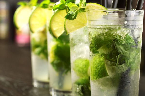 Mint Mojito | 45ml clear white rum  10 whole mint leaves  2 tablespoons sugar  6 lime wedges  Splash of lime-flavoured carbonated drink  Crushed ice