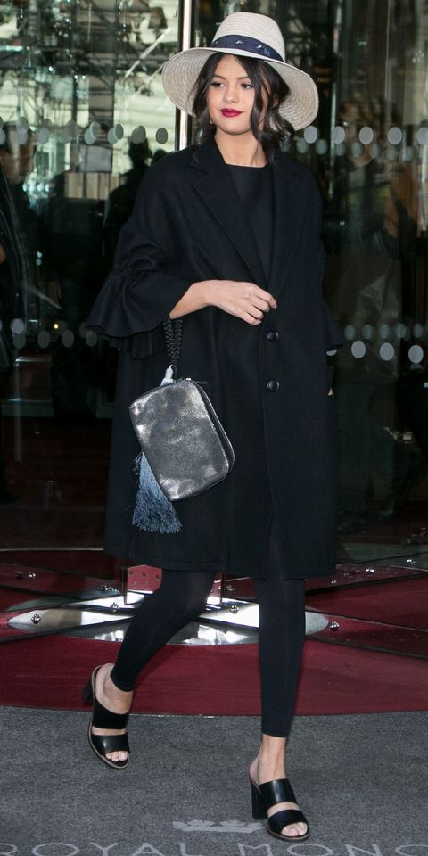Selena Gomez in a black overcoat (layered over black separates) with a wide-brim Maison Michel straw hat.
