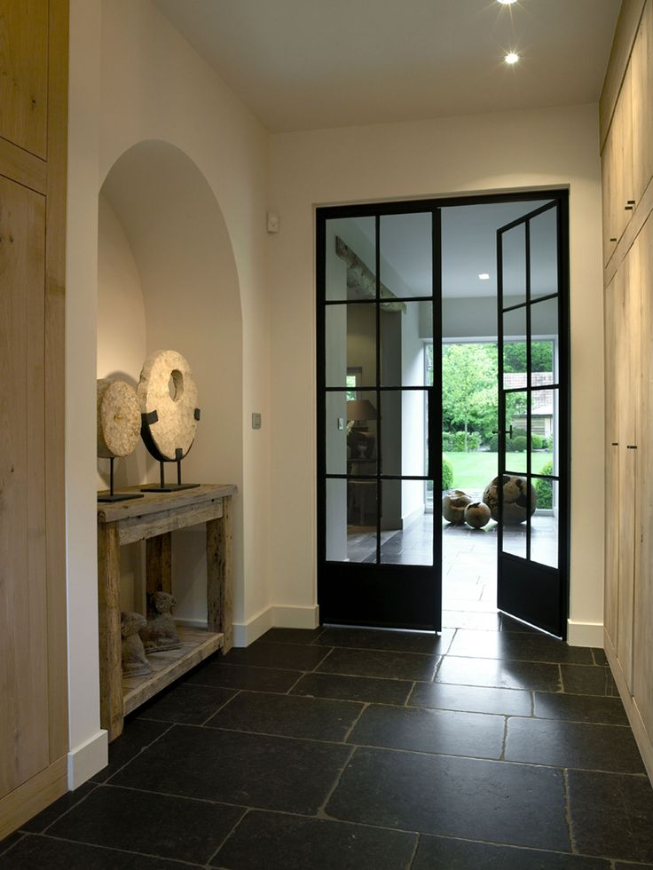 Hallway - SELS NV Belgium - Black iron door with glass, Natural blue stone flore tiles, oak wood closet doors. Natural stone artwork