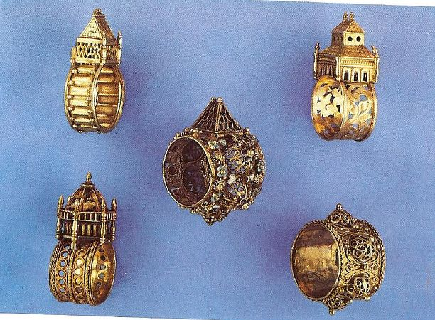 """Antique Jewish Wedding Rings. The goldsmith would engrave something on the exterior of the """"house""""; engravings were also commonly hidden inside, in which case the """"house"""" – or bezel – would slide open. The engraving would usually read Mazal Tov, or the Hebrew initials M.T.  The rings' houses varied in design from castle-like, to square, round or hexagonal. The structures were representations of either the Holy Temple or synagogues in the diaspora."""