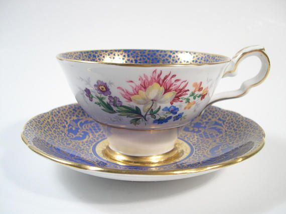 Beautiful tea cup & saucer from Royal Stafford. Royal blue tea cup set and heavy gold filigree. Gold floral design embossed on both pieces, there is also a colorful floral design on the outside of the tea cup. The rims are gilt. The cup measures: 2 1/4 high X 3 7/8 & the saucer