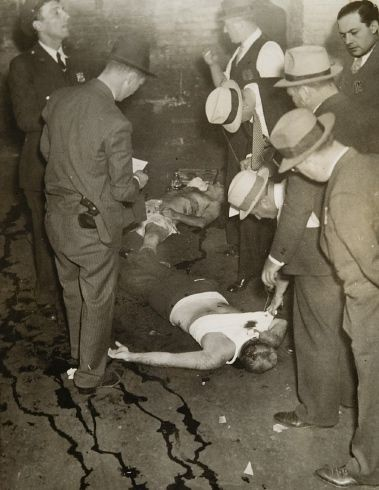 The bodies of Joseph Amberg and his chauffeur, Morris Keesler, lie on the floor of a parking garage located on Christopher and Blake Streets in Brooklyn, NY. They were shot by the members of the notorious Murder, Inc. gang on Sept. 30, 1935.