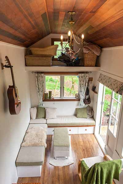 The benches in this tiny house sit on top of deep drawers. The middle bench can serve as an extra seat or a coffee table. They keep the space tidy by stashing seldom-used items in the loft above the living room.