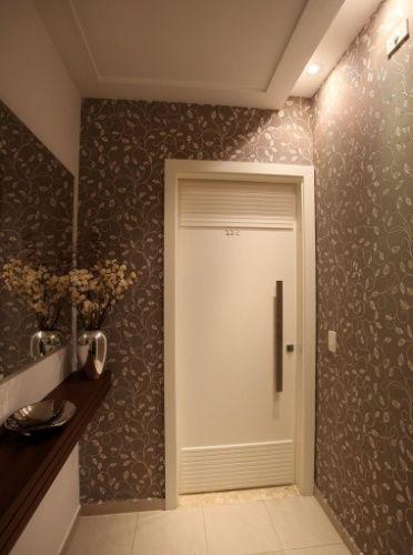 A aplicação do papel de parede floral na parede fez a diferença do hall social assinado pela arquiteta Ana Bartira. Na parede branca (à esq.), um espelho e o aparador de madeira ajudam a compor a decoração. Destaque para o trabalho do forro em sanca que embute a iluminação indireta