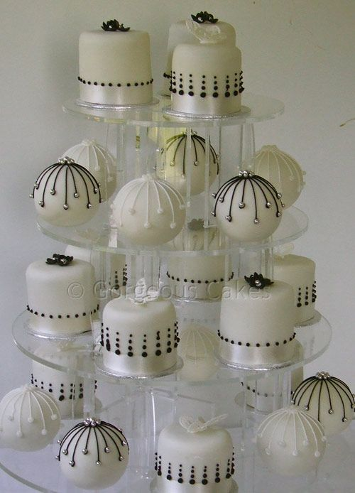 Vyrnwy Baubles    Named for the venue, a chic combination of black and white piped baubles with little cakes decorated with sugar butterflies and blossoms.    There is a minimum order of 20 on individual and bauble cakes.    Ask about boxes to give your bauble cakes as favours