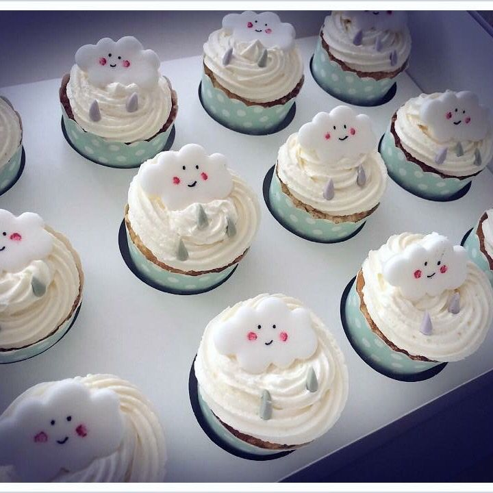 Smiling cloud cup cakes for a rainy themed baby shower. Different coloured icing rain drops on top of white frosting.