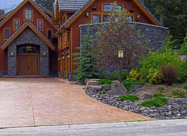 A stamped concrete driveway leads up to a beautiful home for Nice front yard landscaping