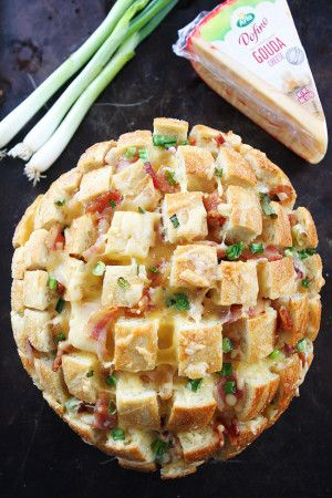 Cheesy Bacon Pull-Apart Bread Recipe on twopeasandtheirpod.com Bread drizzled with garlic butter and stuffed with Gouda, bacon, and green onions. This easy, cheesy bread is perfect for game day, parties, or any day! (Holiday Bake Bread)