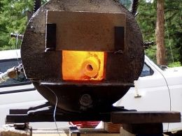 """Homemade forge adapted from a surplus well head. Lined with ceramic wool, bubble alumina, and castable refractory. Measures 14"""" in diameter and 24"""" in length"""