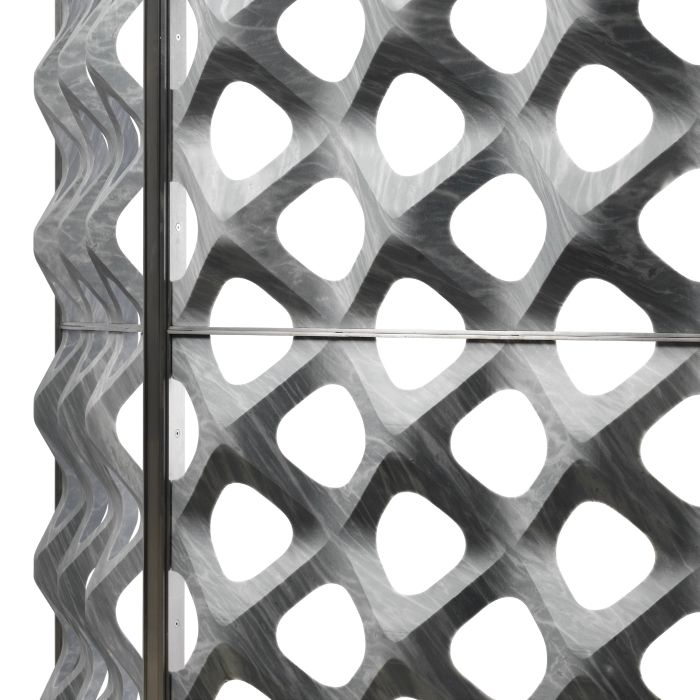 """Enclosed in a metal frame, this perforated stone partition is a fine 3D membrane where marble eludes the limit of its specific weight, reaching a harmonious lightness combined with a strong three-dimensional appeal. The perforations and the fair smooth surface then give the dividing wall an aesthetic feeling of modernity and elegance. Our """"retina"""" space divider from the """"Diaframmi"""" collection."""