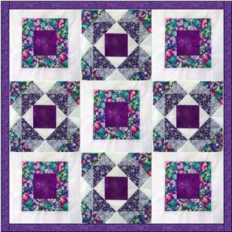 The Marys Block quilt is made with two simple blocks, making a striking overall design using purple, 3 blue fabrics and white.
