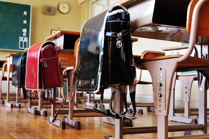 教室の机に掛かるランドセル ランドセルは、日本の多くの小学生が通学時に教科書、ノートなどを入れて背中に背負う鞄である。