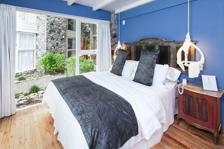 Dormitorio romántico de hotel de bosque y playa en tonos grises y azules. ¡Very original lamp!